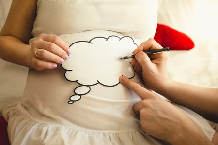 Closeup of photo of man writing on paper sign on wifes pregnant abdomen Stock Photo