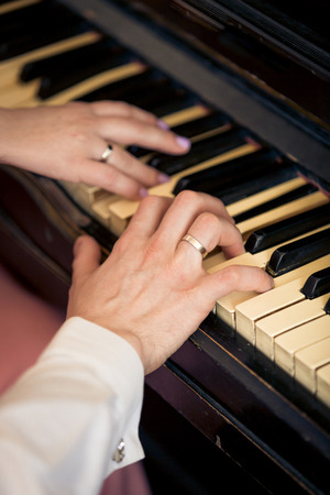 newly married couple: Closeup toned photo of newly married couple playing on piano