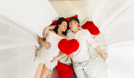 View from top of happy pregnant couple lying on bed with baldachin photo