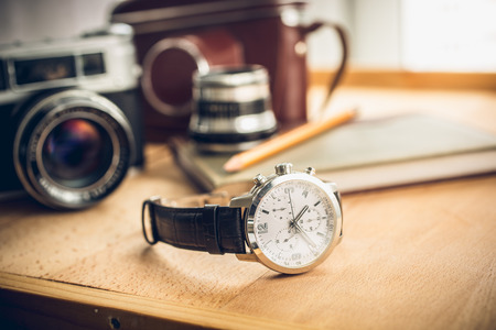 Closeup toned shot of male watches lying on table against photography retro set