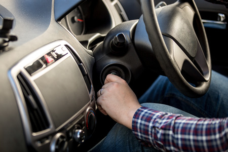 Male driver turning ignition key in right-hand drive car Stock Photo