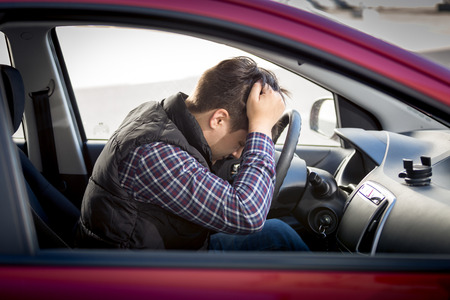 Portrait of stressed man sitting on car drivers seat