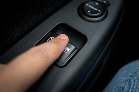 Closeup photo of man pressing button controlling window in car photo