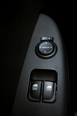 knobs: Closeup photo of knobs controlling windows and mirrors in car Stock Photo