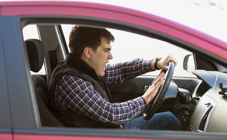 Ritratto del primo piano aggressivo clacson conducente maschio nel traffico Archivio Fotografico