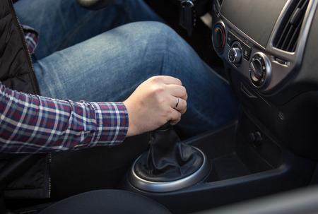 若い男の車でマニュアルのギアボックスのシフトのクローズ アップ ショット