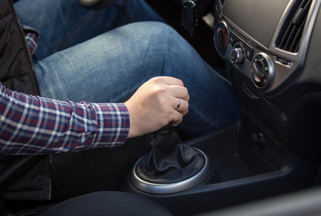 Closeup shot of young man shifting manual gearbox in car Stock Photo