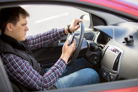 Portrait of young man typing message while driving a car photo
