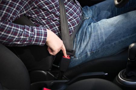 cinturon seguridad: Conductor hombre joven que presiona el botón rojo cinturón de seguridad en el coche