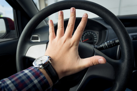 Closeup photo of angry driver honking in traffic Stock Photo