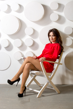 Elegant brunette woman in red dress posing in white wooden chair at studio