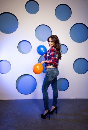 Beautiful smiling woman posing with balloons against colorful background photo