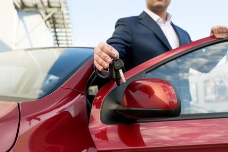 キーを与えて、ハンサムな車のセールスマンのクローズ アップ写真