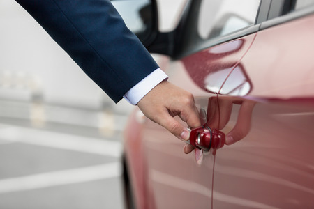 Closeup photo of young businessman pulling car door handle photo