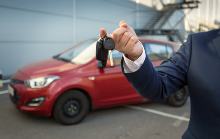 sales manager: Closeup shot of sales manager holding car keys against new car Stock Photo