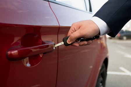 Closeup photo of businessman opening parked car with key