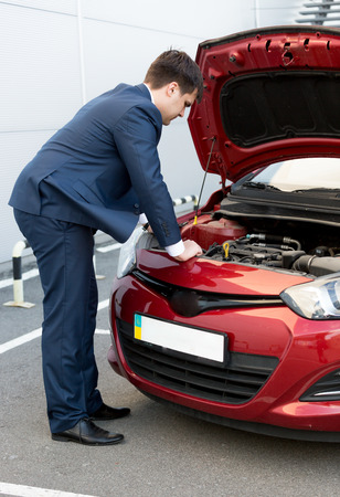 bonnet: Adult man in suit looking under car bonnet