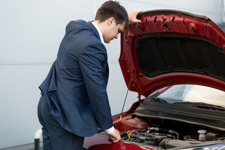 sales manager: Young car sales manager looking under the bonnet of automobile