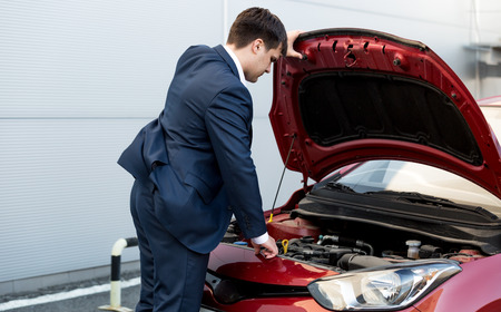 stopped: Young businessman in suit opening bonnet of open car