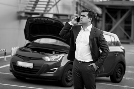 businessman waiting call: Black and white portrait of man calling in technical service to evacuate broken car