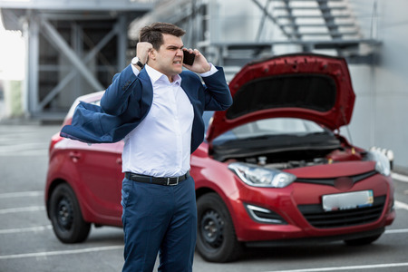 Angry businessman shouting in phone because of broken car photo