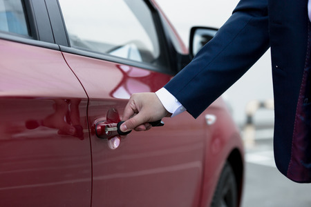 Closeup photo of businessman hand opening car door photo