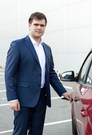 Portrait of handsome young businessman opening car door photo