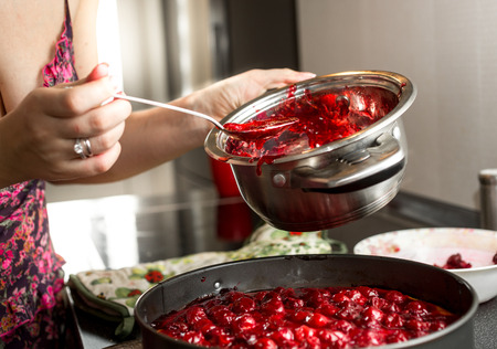 Young housewife making cherry jam in metal saucepan 版權商用圖片
