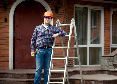 Professional worker posing with metal ladder against building house