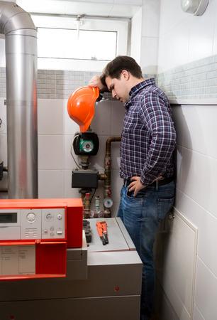 Instalatér s červená čepice pohledu na komplikovaném systému vytápění