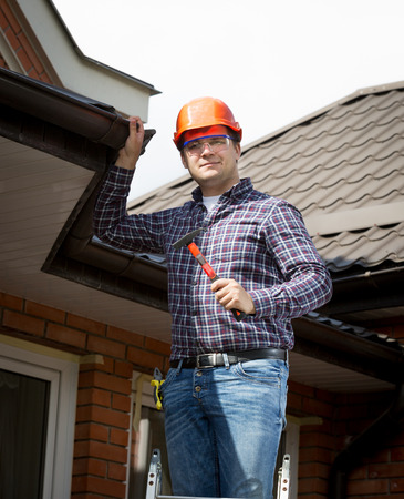 Portrait of handyman standing on high ladder and inspecting house roof