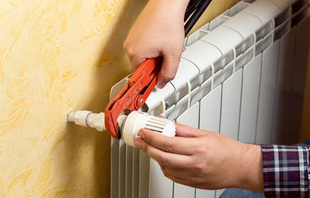 fontanero: Primer disparo del hombre de instalar radiador de calefacción y válvula de conexión
