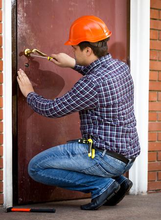Professional carpenter changing lock in heavy metal door