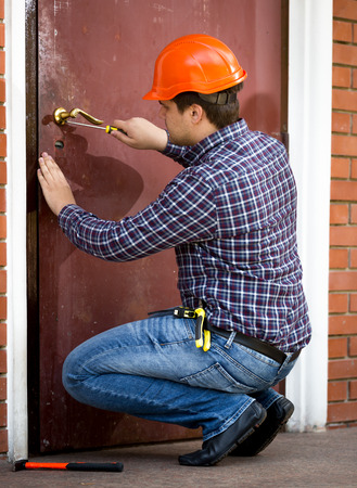 Professional carpenter changing lock in heavy metal door Фото со стока - 41600631