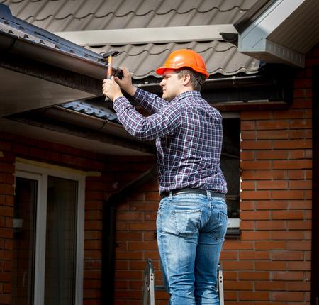 プロの大工が屋根板をハンマーで打って