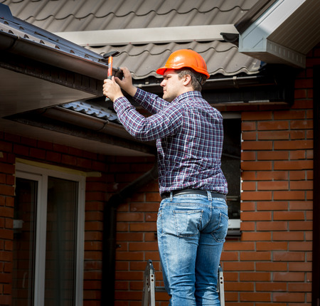 Professional carpenter hammering roof boards with hammer Foto de archivo