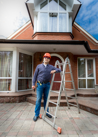 Young smiling worker posing against beautiful newly built house