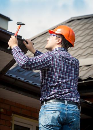 家の屋根の修復作業での大工の肖像画