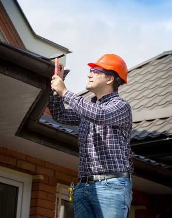 Portrait of young handyman repairing house roof with nails and hammer Standard-Bild