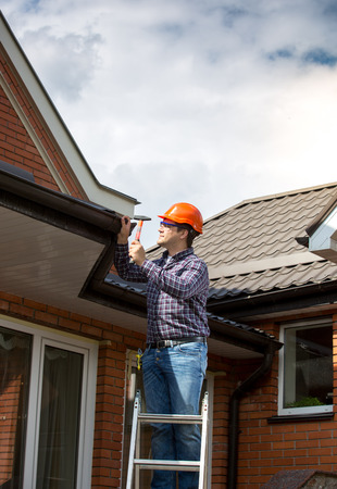 Professional carpenter standing on high ladder and repairing house roof