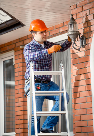 property ladder: Young worker standing on high ladder and changing bulb at outdoor lamp Stock Photo