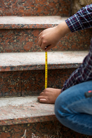 quantity surveyor: Closeup shot of worker measuring height of stone steps