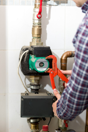 Closeup shot of plumber repairing heating system with red pliers photo
