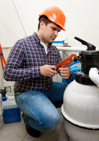Young plumber installing manometer on high pressure barrel