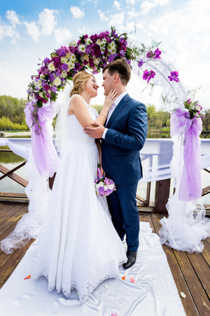 summer dress: Beautiful bride and groom hugging under decorated flower arch Stock Photo