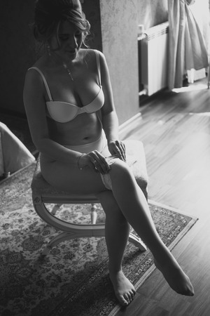 nude woman sitting: Black and white shot of sexy bride putting on stocking at hotel room