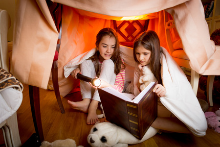 Two cute sisters sitting in house made of blankets and reading book