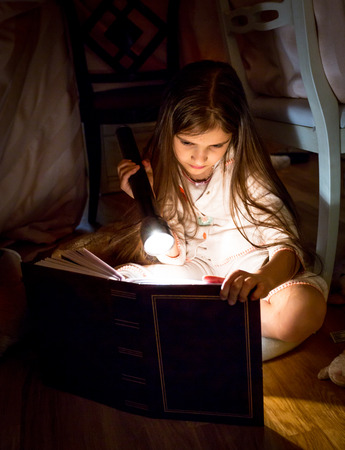 Cute little girl reading book under blanket at night Standard-Bild