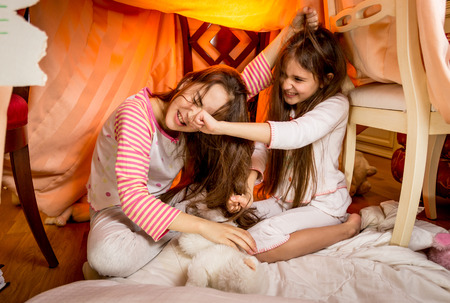 Two little sister having a fight in bedroom