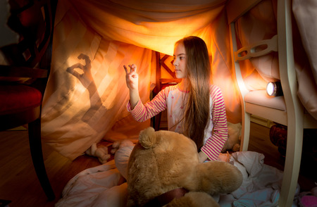 day bed: Cute little girl playing in shadow theater in bedroom at night